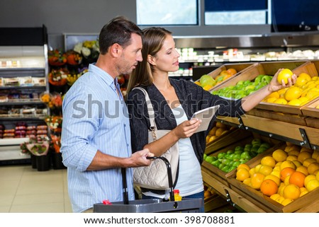 Cute couple choosing groceries together at the supermarket - stock photo