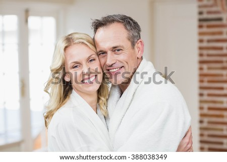 Cute couple cuddling in bathrobes in the kitchen