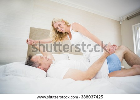 Cute couple cuddling in bed in their room - stock photo