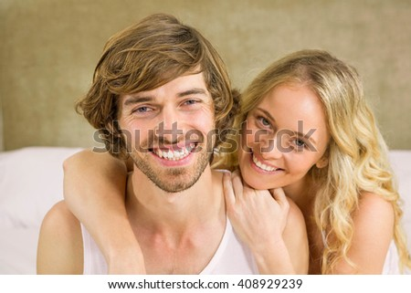 Cute couple cuddling on their bed in the bedroom - stock photo