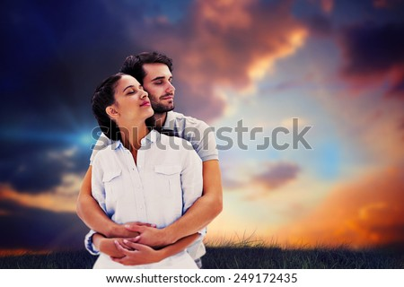 Cute couple embracing with eyes closed against blue and orange sky with clouds - stock photo