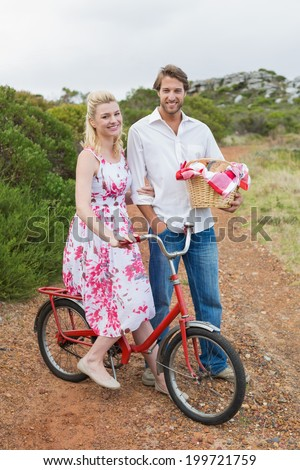 Cute couple going for a picnic smiling at camera on a sunny day