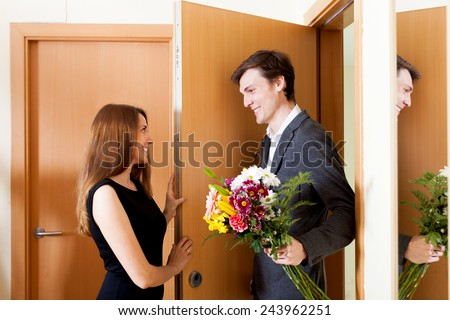 Cute couple greeting in the doorway at home