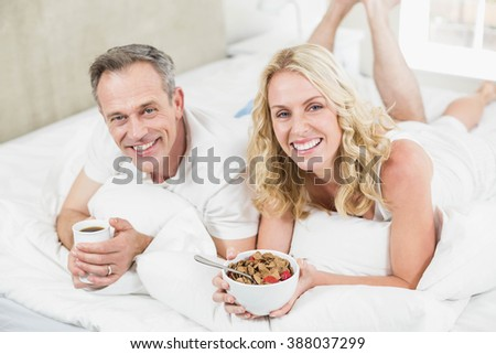 Cute couple having breakfast in bed in their room - stock photo