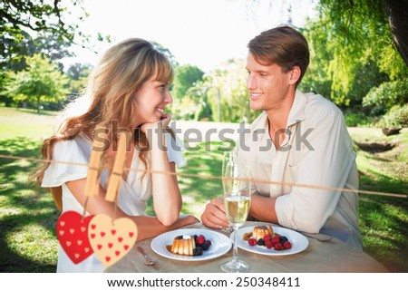 Cute couple having champagne and desert in the park against hearts hanging on the line