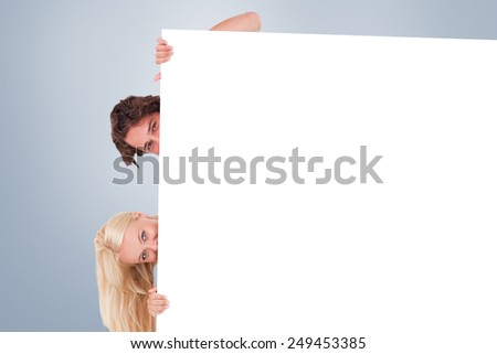Cute Couple hiding behind a whiteboard against grey vignette - stock photo