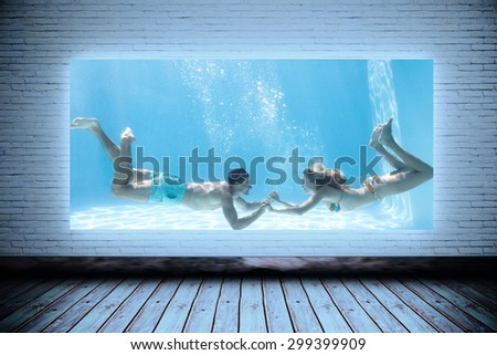 Cute couple holding hands underwater in the swimming pool against room with screen - stock photo