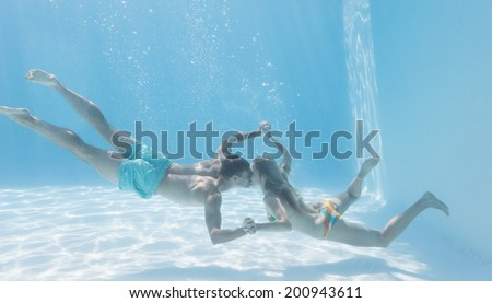 Cute couple holding hands underwater in the swimming pool on their holidays - stock photo