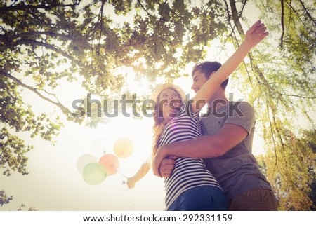 Cute couple hugging and holding balloons in the park on a sunny day - stock photo