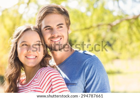 Cute couple hugging in the park on a sunny day - stock photo