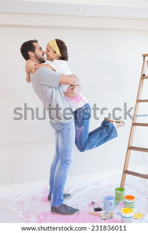 Cute couple hugging while redecorating in their new home - stock photo