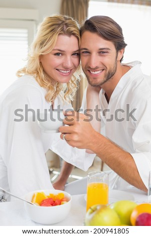 Cute couple in bathrobes having breakfast together smiling at camera at home in the living room