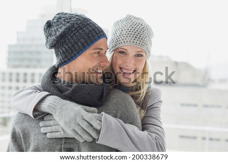 Cute couple in warm clothing hugging woman smiling at camera on a chilly day