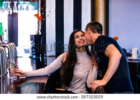Cute couple kissing and having a drink in a bar - stock photo
