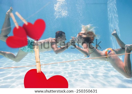 Cute couple kissing underwater in the swimming pool against hearts hanging on a line - stock photo