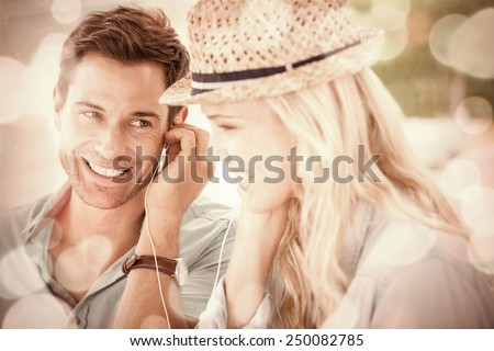 Cute couple listening to music together in cafe on a sunny day in the city - stock photo