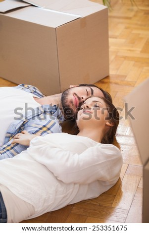 Cute couple lying on the floor in their new home