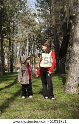 Cute couple of two children standing in a forest - stock photo