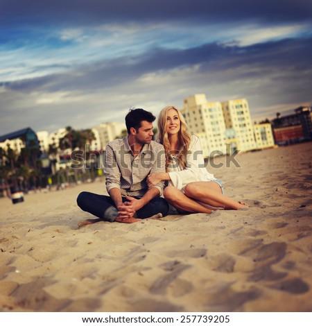 cute couple on beach cuddling while watching sunset - stock photo
