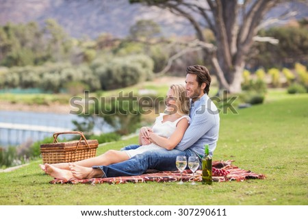 Cute couple on date with arms around lying on a blanket - stock photo