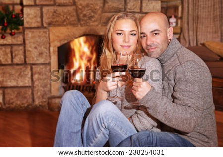 Cute couple on romantic date, beautiful woman with handsome man sitting near fireplace and drinking wine, celebrating Christmas holidays - stock photo