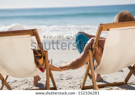 Cute couple on the beach holding hands while lying on their deck chairs - stock photo