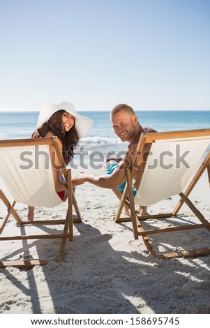 Cute couple on the beach smiling at camera while lying on their deck chairs - stock photo