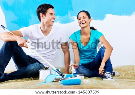 cute couple painting new home together portrait while sitting on wooden floor - stock photo