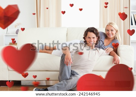 Cute couple posing against love heart pattern - stock photo