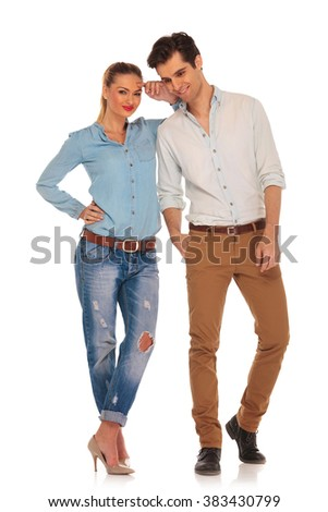 cute couple posing in white isolated studio background. woman with legs crossed looking at the camera while resting arm on his shoulder. man with hand in pocket looks down - stock photo