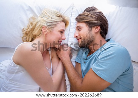 Cute couple relaxing on bed smiling at each other at home in the bedroom - stock photo