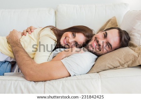 Cute couple relaxing on couch at home in the living room - stock photo