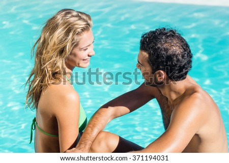 Cute couple sitting at the edge of the pool - stock photo