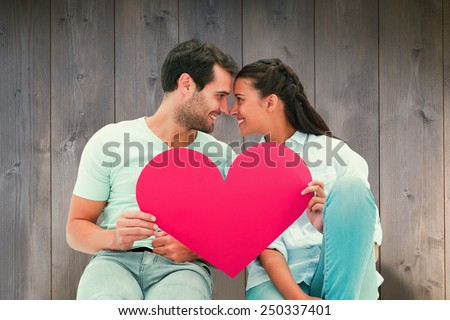 Cute couple sitting holding red heart against wooden planks - stock photo
