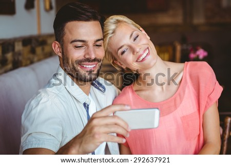 Cute couple sitting in cafe looking at smartphone on a sunny day - stock photo