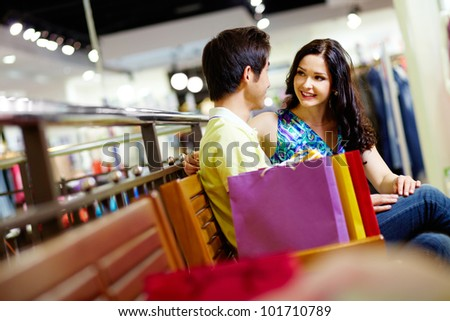 Cute couple sitting on a bench in the shopping mall and admiring each other - stock photo