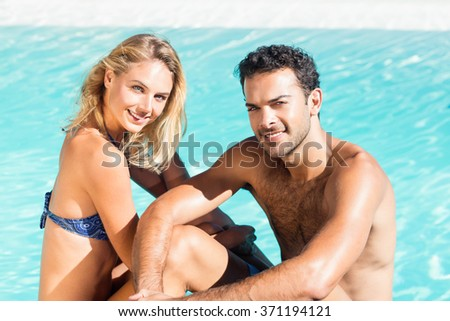 Cute couple sitting on the edge of the pool - stock photo