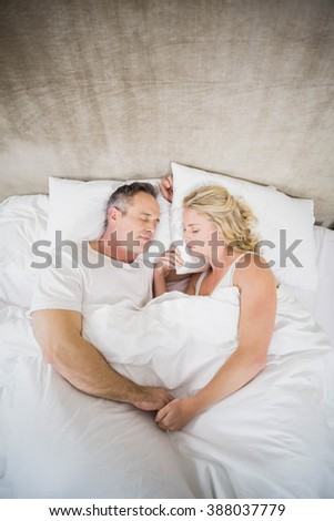 Cute couple sleeping in their bed in their room - stock photo