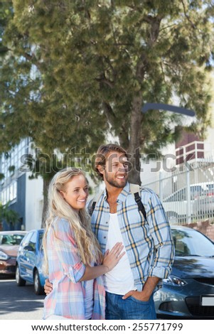 Cute couple standing and smiling on a sunny day in the city - stock photo