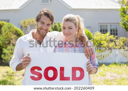 Cute couple standing together in their garden holding sold sign on a sunny day - stock photo