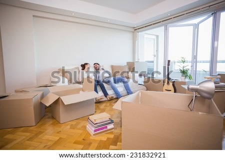 Cute couple taking a break from unpacking in their new home - stock photo