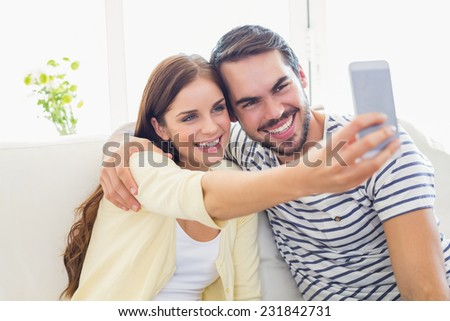 Cute couple taking a selfie on couch at home in the living room - stock photo