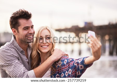 cute couple taking selfies together on beach - stock photo