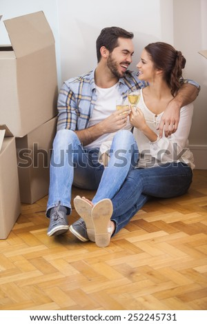 Cute couple toasting with champagne on floor in their new home - stock photo