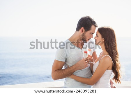 Cute couple toasting with champagne on their balcony - stock photo