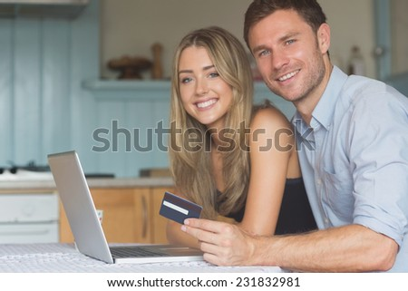 Cute couple using laptop together to shop online at home in the kitchen - stock photo