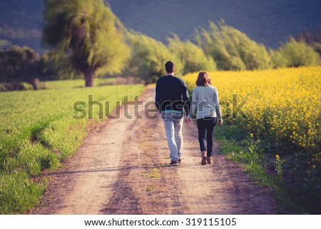 Cute couple walking in a beautiful path in nature - stock photo