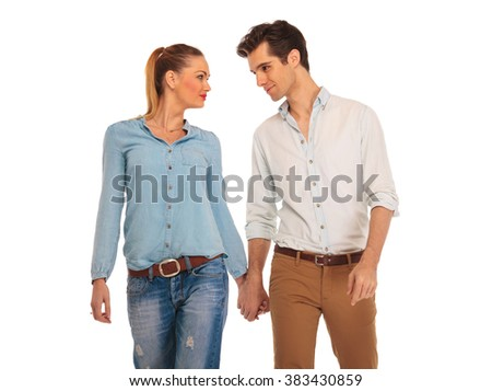 cute couple walking in white isolated studio background, holding hands and looking at each other - stock photo