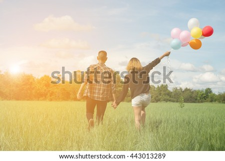 Cute Couple with colorful Balloons in meadow on thailand