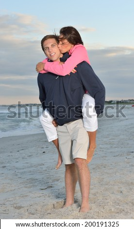 Cute couple with female on the back being carried by man on beach at sunset - in sand with surf behind them woman kissing man on cheek